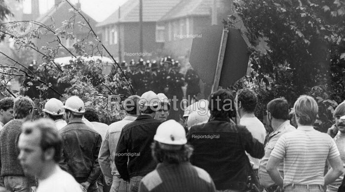 Pickets behind their barricade with police beyond. Mass picket in conflict with police who had got a scab into the pit. Pit Lane Rossington Colliery. Miners strike, Doncaster. - John Harris - 1984-07-09