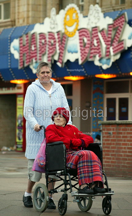 Elderly holidaymaker and carer wait to cross the road, Happy Dayz arcade on the Golden Mile, Blackpool seafront. - John Harris - 2003-10-08