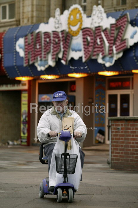 Elderly holidaymaker on a motorised scooter going past Happy Days amusement arcade on the Golden Mile, Blackpool seafront. - John Harris - 2003-10-08