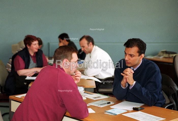 Workers looking for a job- discussing job vacancies Employment Service at an Employment Centre in the works canteen at Rover Longbridge, Birmingham. The scale of the redundancies are unknown. - John Harris - 2000-04-05