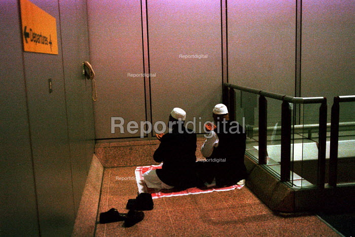 Muslim men praying to Mecca at Heathrow Airport. - John Harris - 2000-03-29