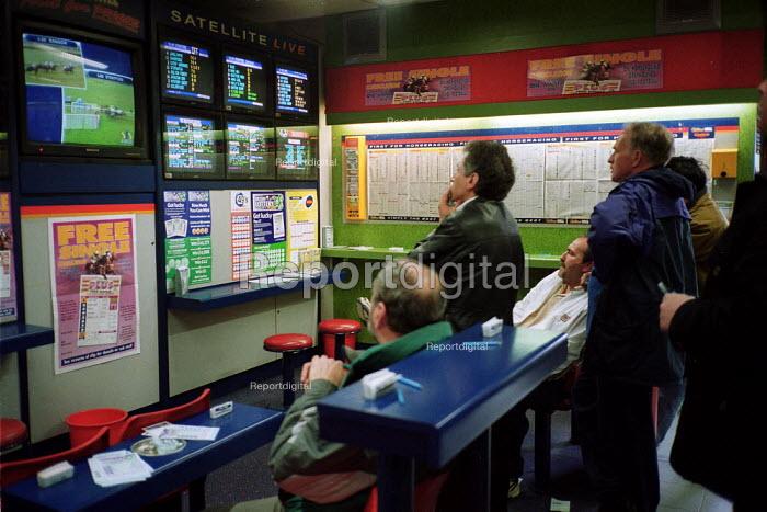 Punters watching a race at Ladbrokes betting shop. - John Harris - 2000-04-14