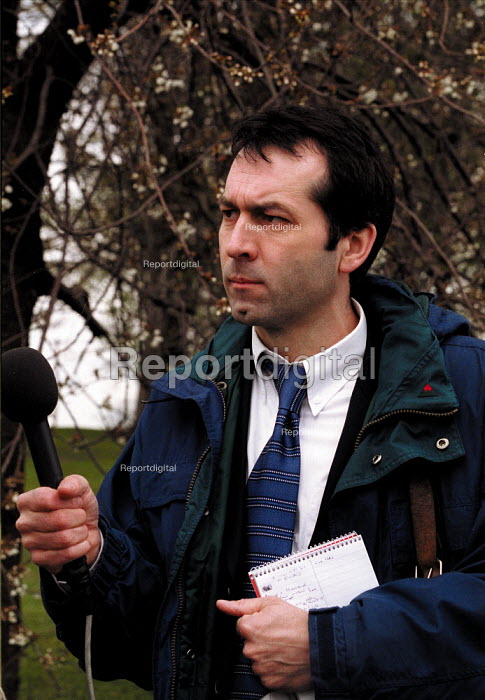 Radio journalist with microphone recording an outside broadcast interview. - John Harris - 2000-04-18