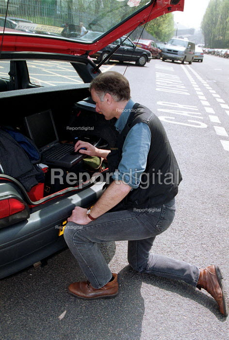 Newspaper photographer sending digital pictures from a laptop computer and mobile phone in the boot of his car. Longbridge - John Harris - 2000-05-09