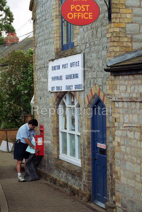 Postal worker collecting post from rural village postbox outside a post office. - John Harris - 2000-05-18