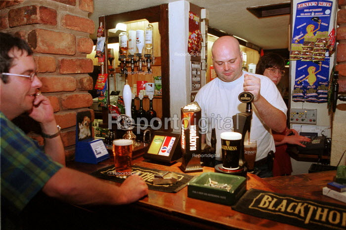 Barman pouring a pint of Guinness in a pub. - John Harris - 2000-05-30