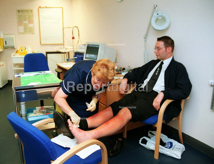 Nurse treating patients sun burn symptoms at NHS walk-in centre in Boots Birmingham, which offers assessment by an experienced NHS nurse who can give healthcare advice, information and treatment. No appointment is necessary. - John Harris - 2000-06-16