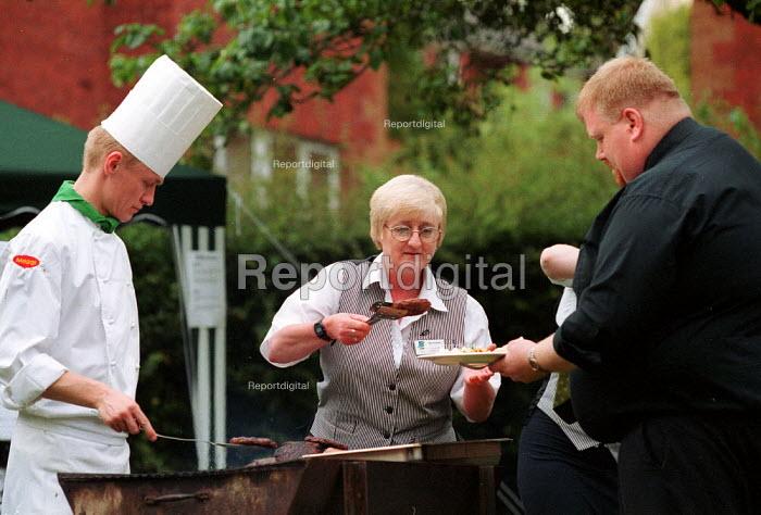 Part time women catering worker serving food. - John Harris - 2000-07-07