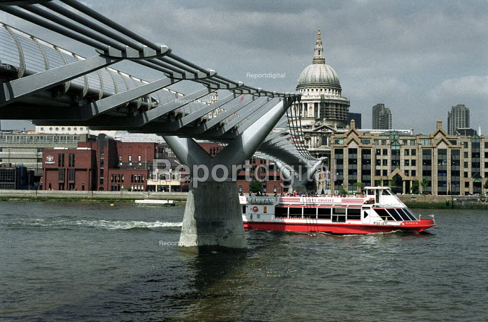 Tourist river boat traveling under the Millennium Bridge, with St Paul's in the background. - John Harris - 2000-08-11