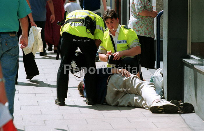 Police helping collapsed drunk in the street. - John Harris - 2000-07-29