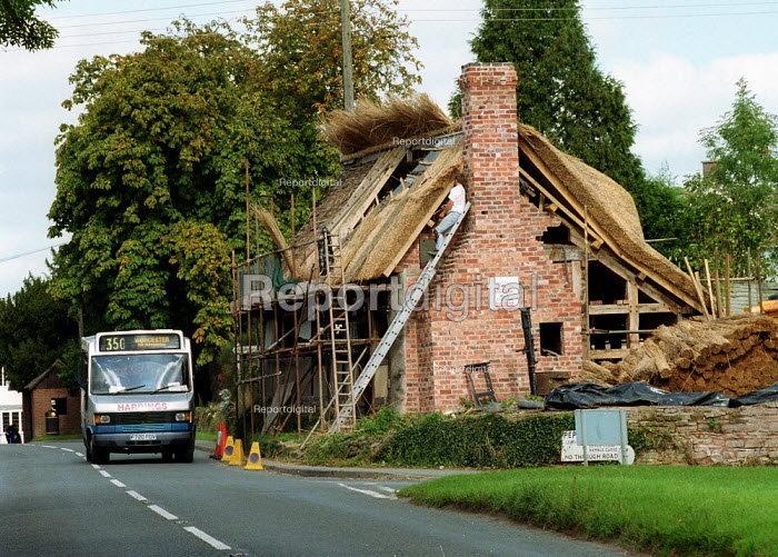 Rural transport, a mini bus takes passengers from a bus stop in a Worcestershire village past a cottage being re thatched. - John Harris - 2000-10-07