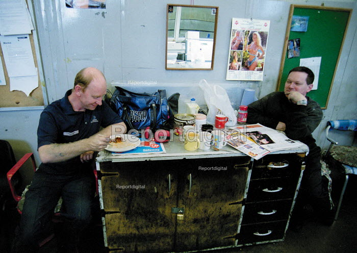 Workers take a lunch break in control room, eating and reading trade press. - John Harris - 2001-01-16