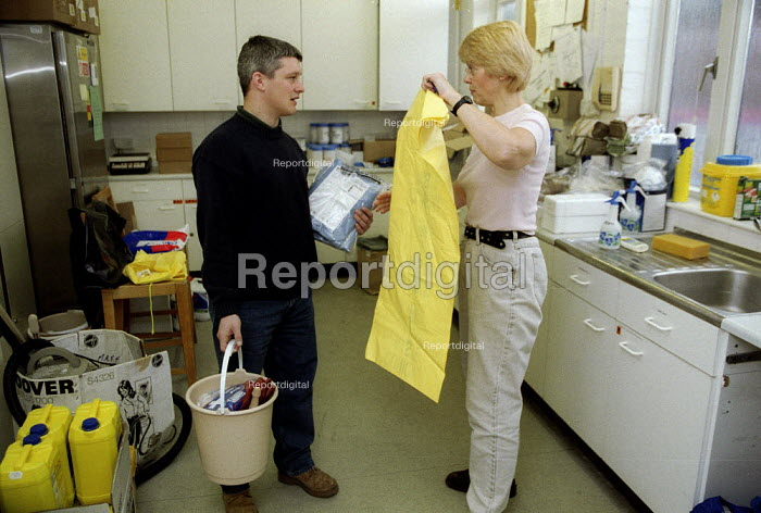 Maff Animal Health Officer equipping a collegue with protective clothing before going out on inspections for symptoms of foot and mouth disease in an at risk area. - John Harris - 2001-03-28