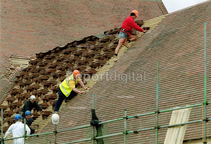 Supervisor watching roofers laying roof tiles. - John Harris - 2001-04-11