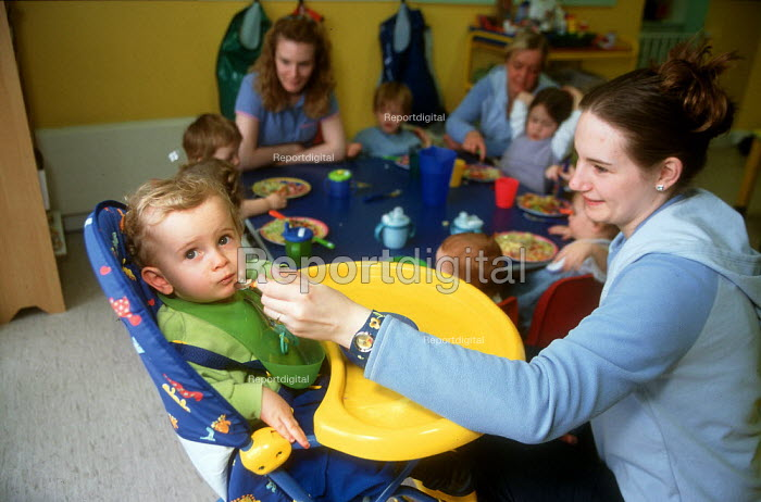 Nursery assistant feeding a toddler lunch at a day time nursery. - John Harris - 2001-04-10