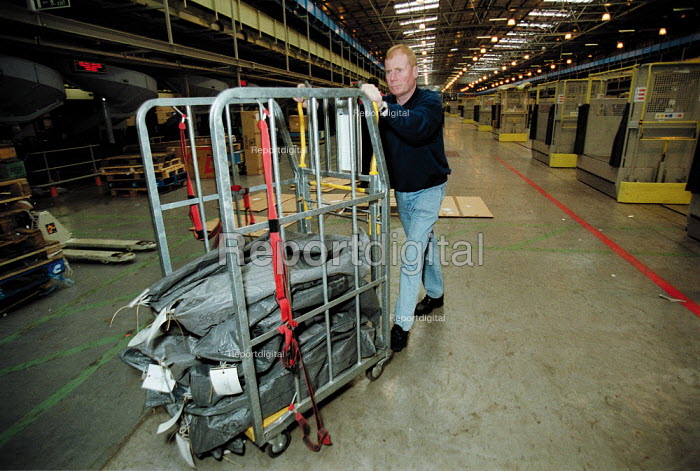 Post Office worker moving mail bags. Post Office Parcel Force Royal Mail Coventry Hub distribution. - John Harris - 2001-05-10