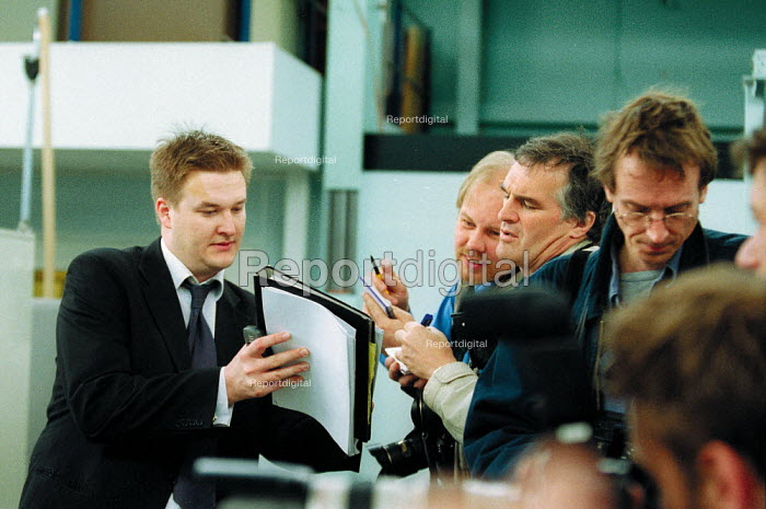 Labour Party press officer helping press photographers, general election campaign. - John Harris - 2001-05-10