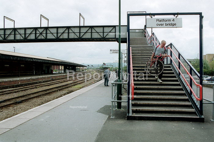 Passenger carrying bicycle down steps of a footbridge over railway lines to a platform. - John Harris - 2001-05-19