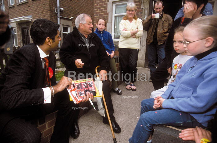 Labour candidate Parmjit Dhanda talking to family and neighbors on a housing estate. Labour Party general election Gloucester. - John Harris - 2001-05-19