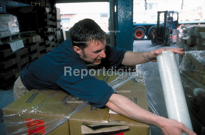 Worker shrink rapping boxes of ceramic plates on a palet for the loading onto a lorry with a fork lift truck, at Churchill ceramics factory in the Potteries, Stoke on Trent. - John Harris - 2001-06-14