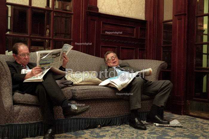 Businessman reading newspapers and sleeping on a settee in a Hotel lobby. - John Harris - 2000-09-20