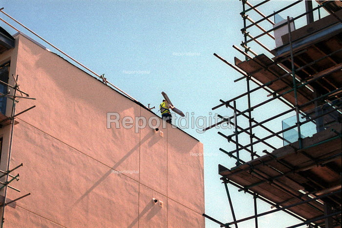 Construction worker carrying materials with safety harness on roof. New flats Bristol. - John Harris - 2001-08-30