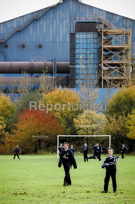Schoolboys playing football on a pitch near a steelworks Cardiff Comprehensive School South Wales. - John Harris - 2001-11-19