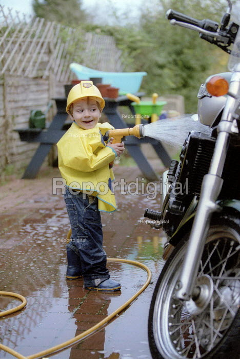 Toddler at 2yrs 10 months playing with garden hose, cleaning a very large capacity Triumph motorcycle. - John Harris - 2002-03-28