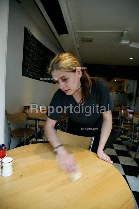 Waitress cleaning a table down. Cafe restaurant Stratford on Avon. - John Harris - 2003-05-20