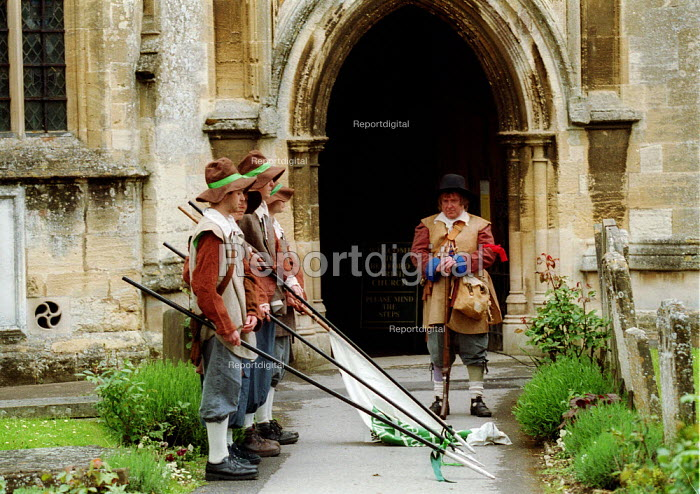 Sealed Knot English soldiers of the New Model Army with lowered standards in honour of the three leveller soldiers shot in against the church wall in 1649. Churchyard, 29th Levellers Day Burford Oxfordshire. - John Harris - 2003-05-17