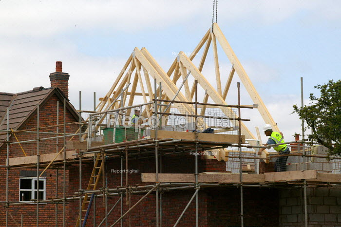 Construction workers fitting A frame roof supports to new build housing on a brownfield site using a crane. Stratford on Avon - John Harris - 2003-06-24