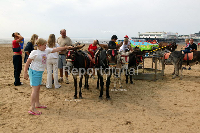 Children riding donkeys on the beach, Weston Super Mare in the hottest temperatures. - John Harris - 2003-08-04