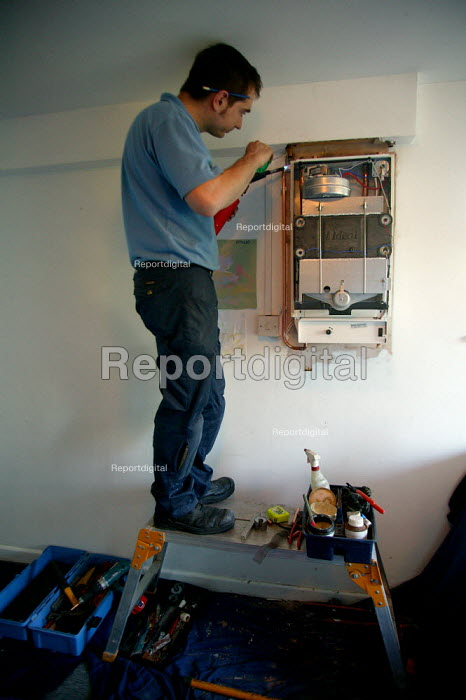 A British Gas Heating Installation Engineer fitting a new boiler using a propane blowtorch to solder pipe joints. - John Harris - 2003-10-23