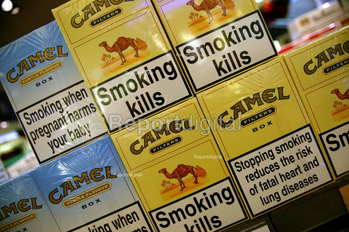 Cartons of duty free Camel cigarettes with statutory health warning of the dangers of smoking, which increases the risk of fatal heart and lung diseases. Amsterdam Airport. - John Harris - 2003-11-25
