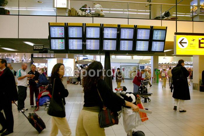 Passengers and departure board, Amsterdam Airport. - John Harris - 2003-11-22