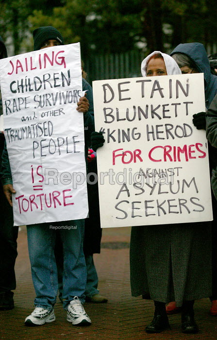 Asylum seekers holding placards protesting Blunkett King Herod for jailing asylum seekers. Campaign to close Campsfield. Protest marking the 10th anniversary of the Campsfield Detention Centre in Oxfordshire used to imprison asylum seekers. - John Harris - 2003-11-29
