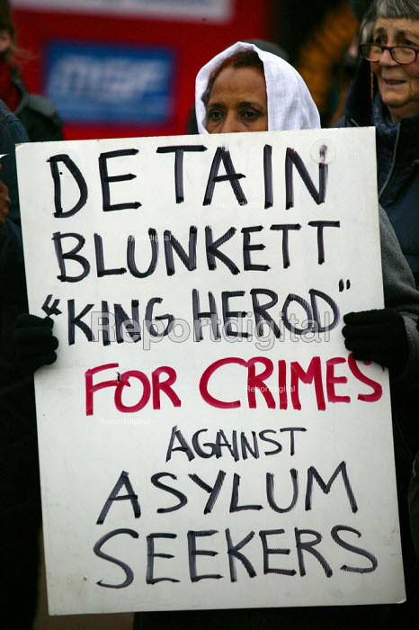 Asylum seekers holding placards protesting Blunkett King Herod for detaining asylum seekers. Campaign to close Campsfield. Protest marking the 10th anniversary of the Campsfield Detention Centre in Oxfordshire used to imprison asylum seekers. - John Harris - 2003-11-29