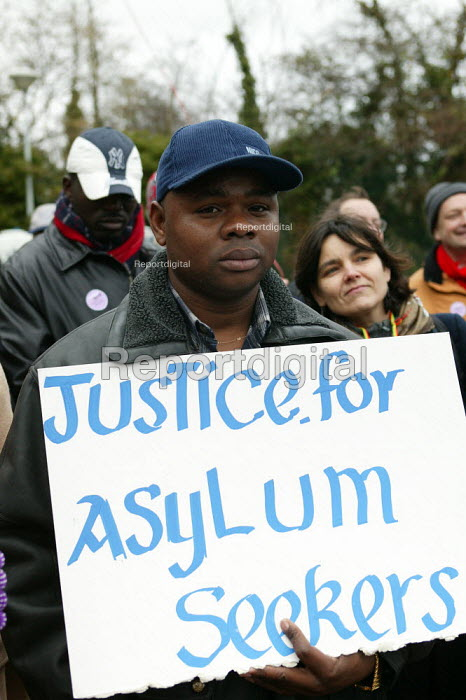 Asylum seekers holding placards Justice for Asylum Seekers. Campaign to close Campsfield. Protest marking the 10th anniversary of the Campsfield Detention Centre in Oxfordshire used to imprison asylum seekers. - John Harris - 2003-11-29