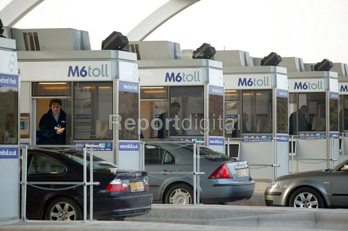 Worker in a Toll Booth as a driver pays. M6 Toll Road is the first tolled motorway in Britain, and is intended to reduce the congestion on the M6. Birmingham Northen Relief Road Weeford Toll booths, West Midlands. - John Harris - 2003-12-09