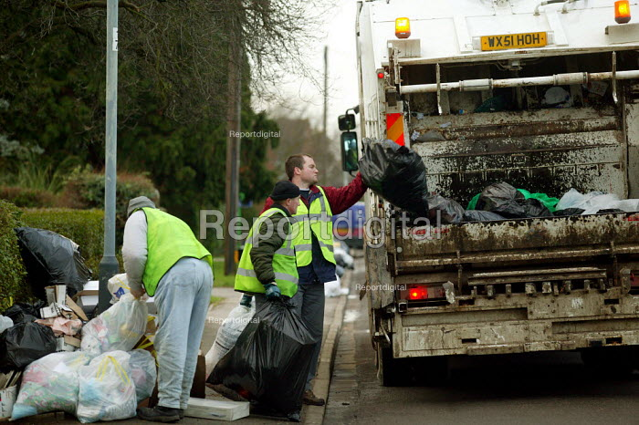 Black plastic rubbish bags piled on the pavement being collected in lifted in a collection lorry. - John Harris - 2003-12-29