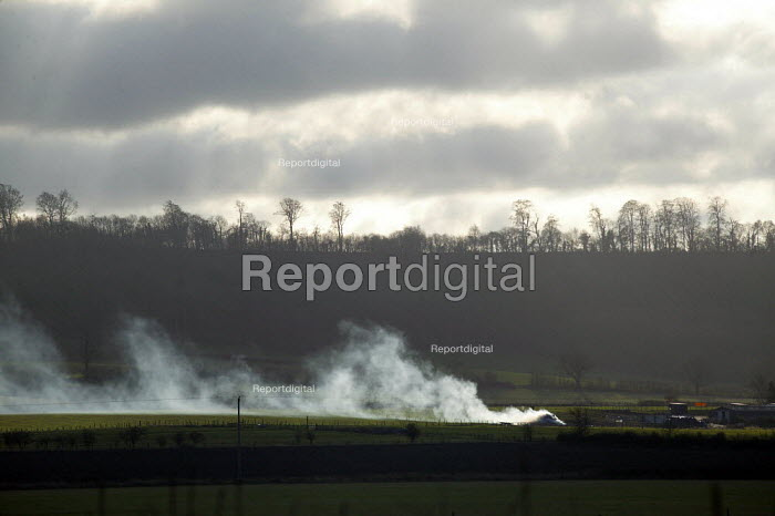 Smoke from a bonfire on a farm, with a treeline and a winter sky, Warwickshire. - John Harris - 2004-01-16