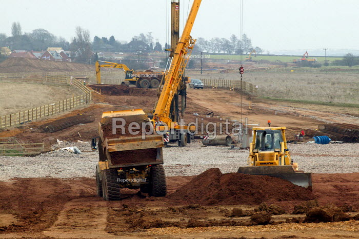 Earth moving equipment and cranes excavating a new road to new housing on the edge of town. Stratford on Avon Warwickshire. - John Harris - 2004-03-03
