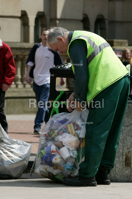A council worker emptying rubbish from a litter bin. Birmingham City centre. - John Harris - 2004-05-22