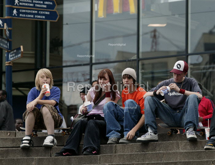 Teenagers sitting around outside McDonalds eating icecream, Birmingham City centre. Saturday. - John Harris - 2004-05-22