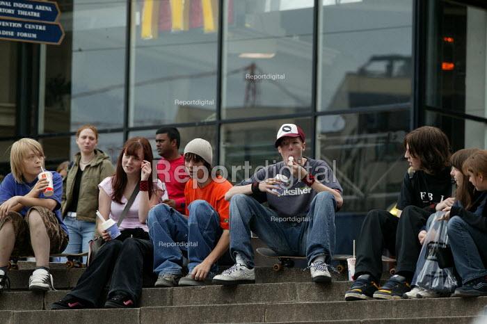 Teenagers sitting around outside McDonalds eating icecream, Birmingham City centre. Saturday. - John Harris - 2004-05-22