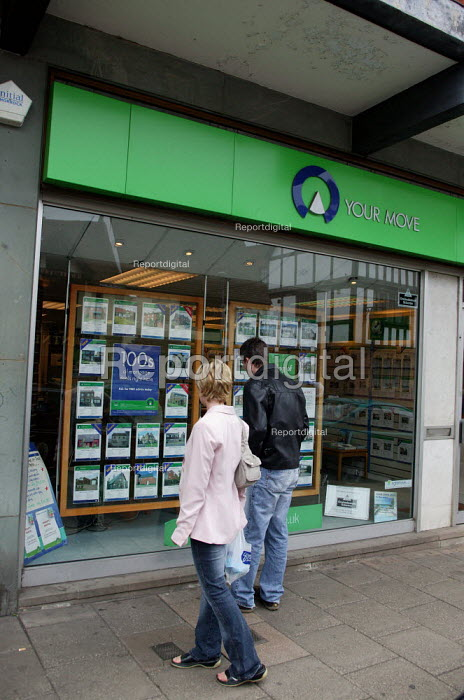 A couple looking at houses for sale in the window of an estate agent. - John Harris - 2004-06-05