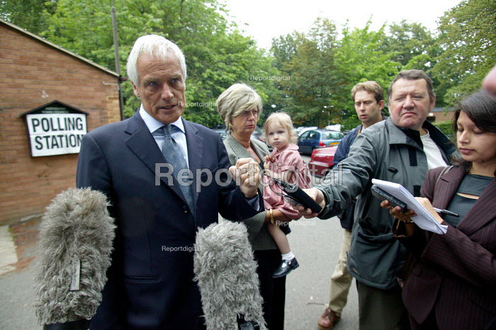 Robert Kilroy Silk UKIP (UK Independence Party) with grandaughter Seraphina and wife Jan outside Polling Station being interviewed by the press. - John Harris - 2004-06-10