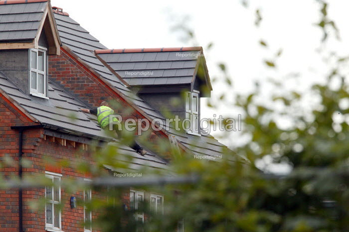 Roofing contactor sliding down the on the roof of new house without a hard hat, Stratford upon Avon - John Harris - 2004-08-27