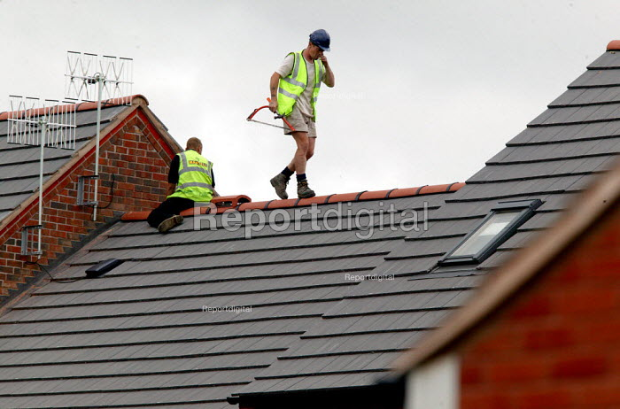 Roofing contractors on the roof of new houses, without harness or hard hat, Stratford upon Avon. - John Harris - 2004-08-27