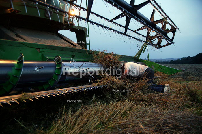 Farmer unblocking his combine harvester. Working late to reap the harvest. Warwickshire. - John Harris - 2004-09-02